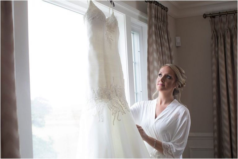 NJ wedding Photographer captures Bride looking at wedding Dress