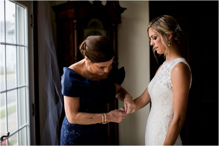Mother of bride putting jewelry on the bride
